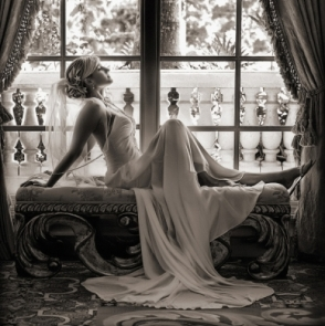 Bride resting on a bench in front of a window at the Ritz Carlton in Sarasota